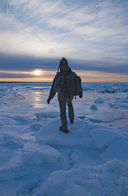 USA, Massachusetts, Cape Cod, Eastham, Man balancing on sea ice at dusk