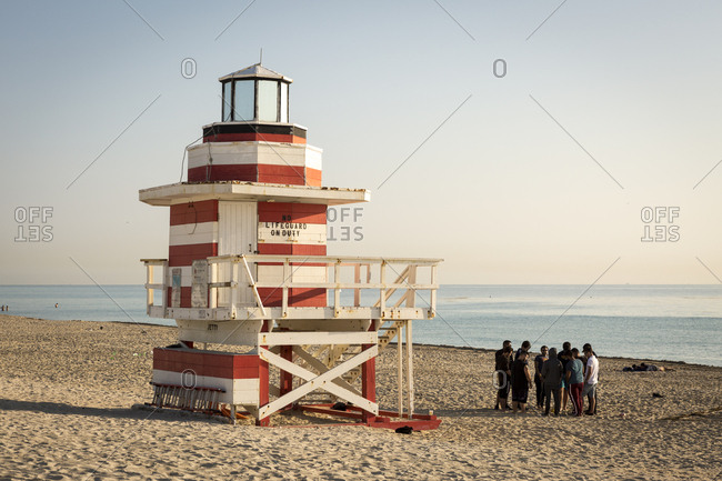 Miami Beach, Florida - 18 March 2018: A group of men gather by one of Miami Beach's iconic lifeguard towers