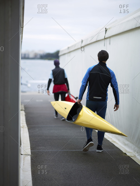 Rear view of two male athletes in swimming sportswear going towards river and carrying kayaks