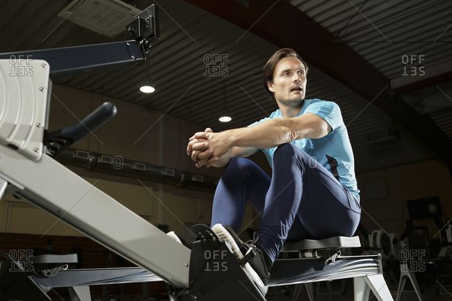 Low angle view of Caucasian male athlete sitting on modern indoor rower and resting after training