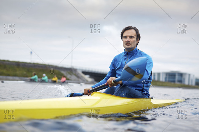Middle-aged athletic Caucasian man moving along the channel in yellow kayak and looking into the distance