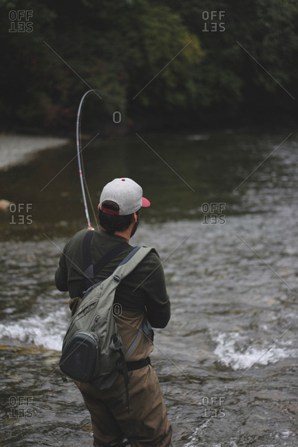 Fisherman tries to reel in big fish on the river in the fall