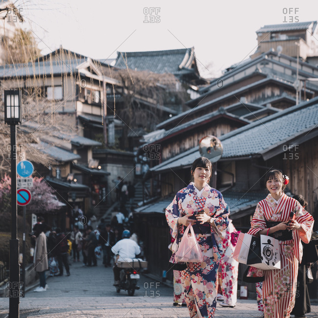 Kyoto, Japan - March 12, 2018: Visitors in traditional kimono carrying bags of souvenirs on Matsubara shopping street leading to Kiyomizu temple