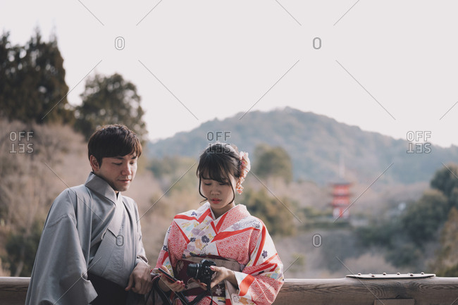 Kyoto, Japan - March 12, 2018: Couple dressed in traditional yukata and kimono leaning against railing with pagoda of Kiyomizu temple in background