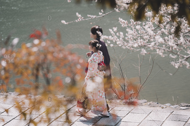 Kyoto, Japan - March 13, 2018: Young couple dressed in traditional clothing walking arm in arm by a lake at the beginning of cherry blossom season