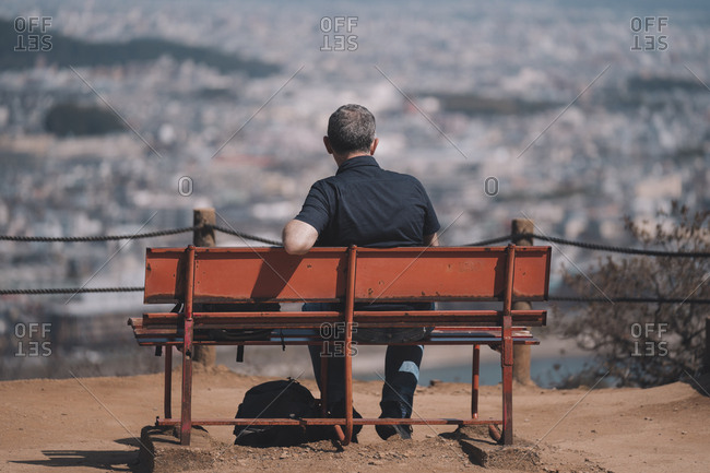 Rearview of tourist sitting on hilltop bench looking at city of Kyoto laid out below