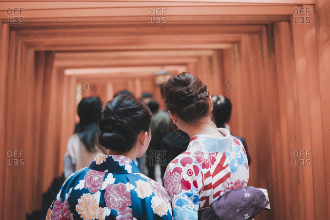 Rearview of women dressed in kimono taking selfie beneath the torii gates at the entrance of Inari Shrine in Kyoto, Japan