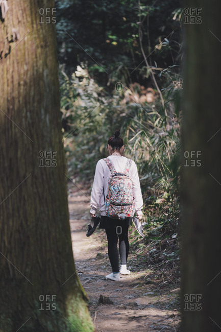 Kyoto, Japan - March 14, 2018: Rearview of woman walking along mountain path without shoes