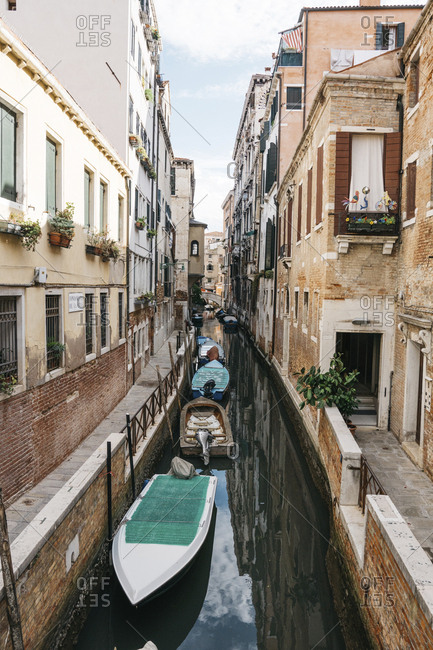Italy, Venice - August 11, 2017: Boats moored in canal amidst buildings in city