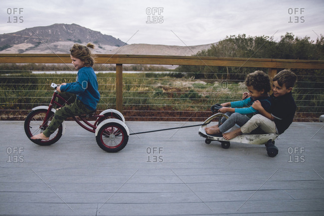 Boy pulling toy car with friends while riding tricycle on floorboard