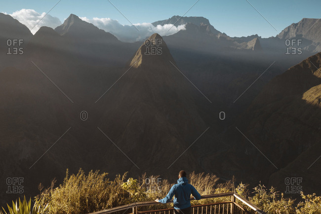 Rear view of man looking at mountains while standing on observation point
