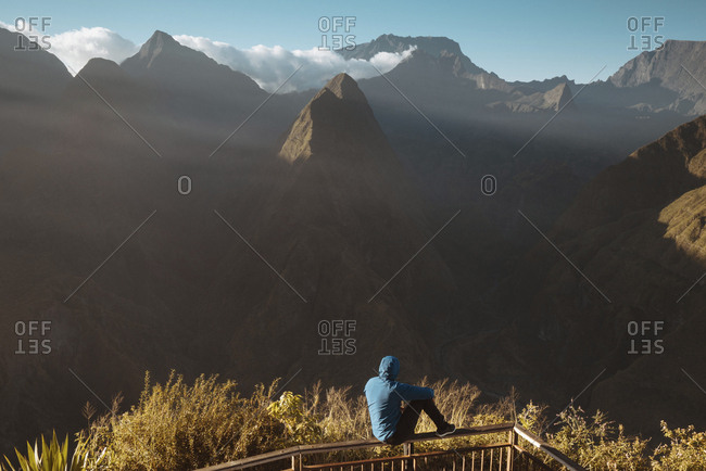 Rear view of man looking at mountains while sitting on observation point