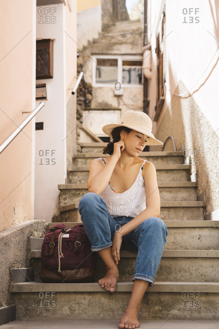 Thoughtful tourist wearing hat while sitting by backpack on steps in city