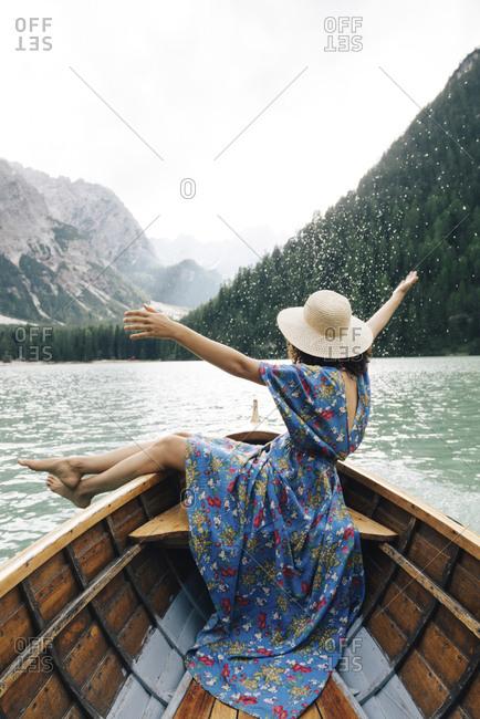 Happy woman enjoying rowboat riding over lake against mountains
