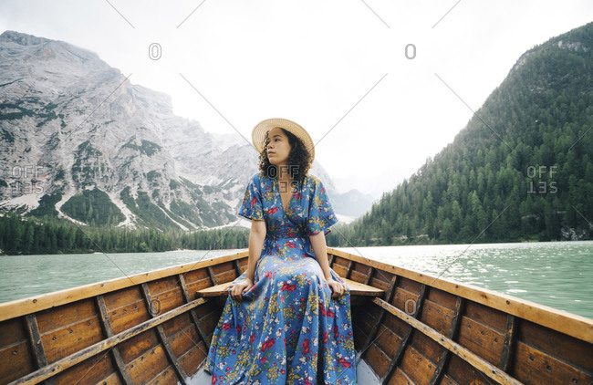 Woman looking away while sitting in rowboat over lake against mountains