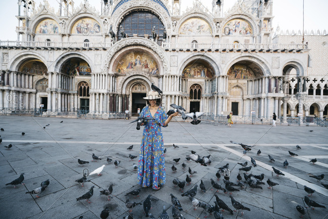 Tourist standing amidst perching birds on footpath against St Mark's Basilica