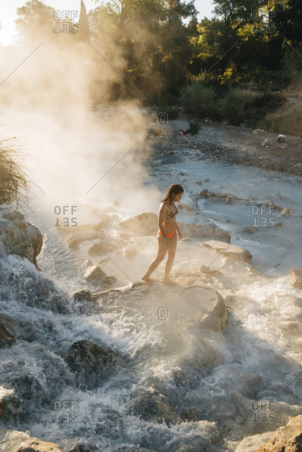 High angle view of woman walking on rock in steam emitting thermal pool