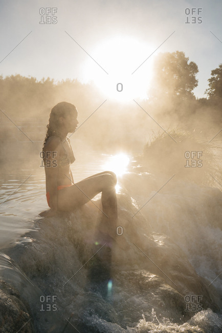 Side view of woman sitting on rocks in steam emitting thermal pool during sunny day