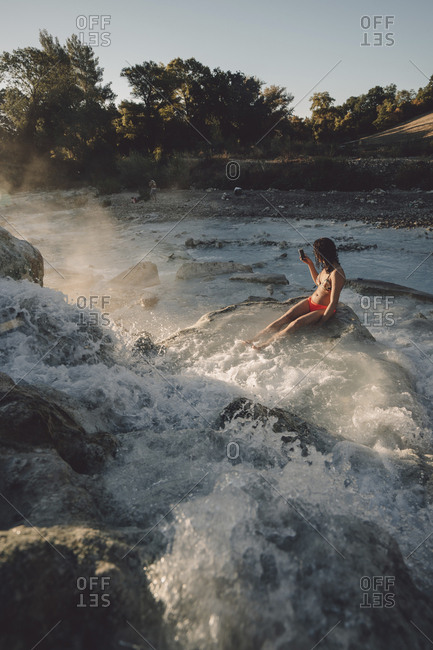 High angle view of woman sitting on rocks while enjoying in steam emitting thermal pool