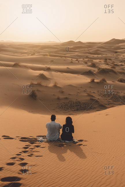 Rear view of friends sitting on sand at Sahara Desert against sky during sunset