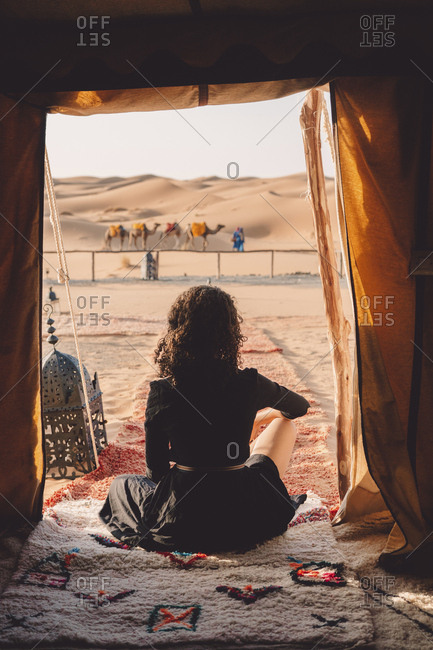 Rear view of woman sitting on blanket at Sahara Desert seen through tent