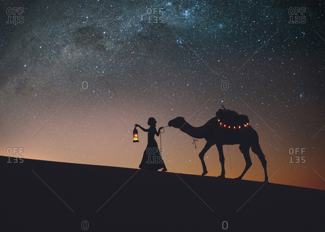 Silhouette woman with camel walking at Sahara Desert against star field