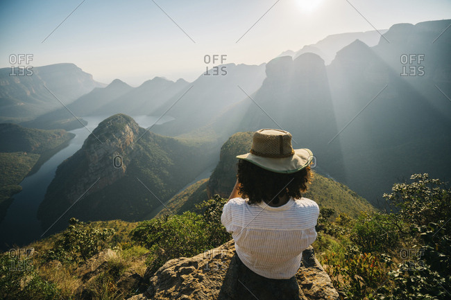 Rear view of woman wearing hat looking at view while sitting on mountain against sky during sunny day