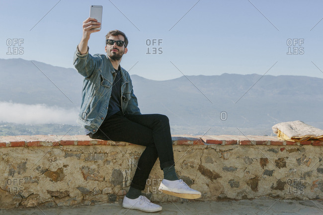 Man photographing while sitting on retaining wall against clear sky