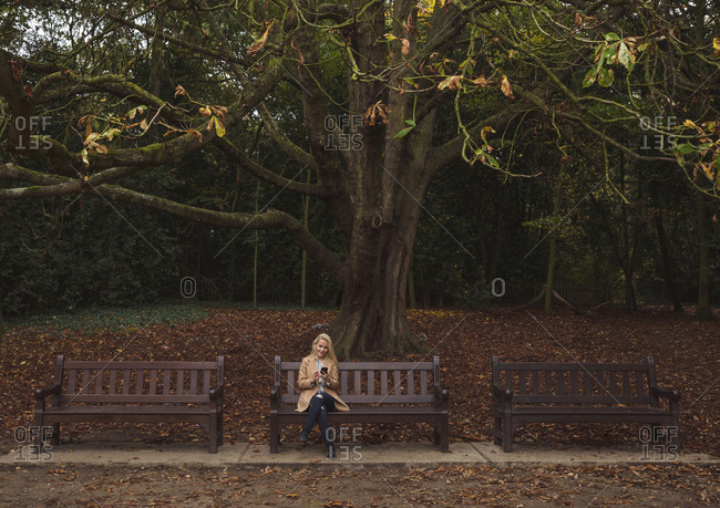 Woman sitting on park bench against tree during autumn