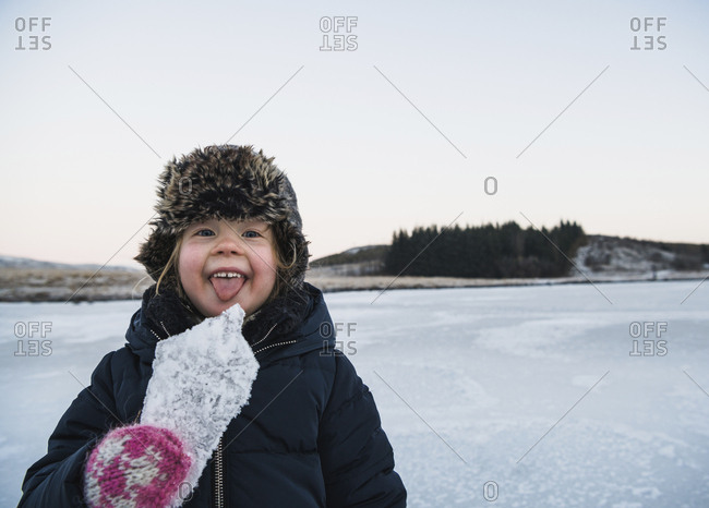 Portrait of playful girl sticking out tongue while holding ice