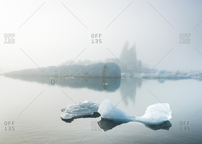 Scenic view of icebergs in sea during foggy weather