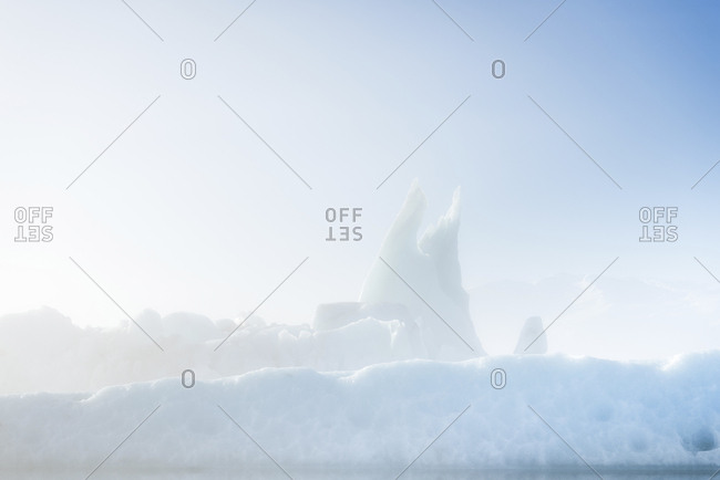 Tranquil view of icebergs against sky during foggy weather