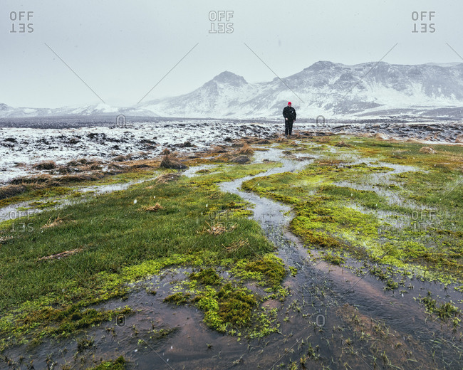 Mid distance view of hiker standing on field against snowcapped mountains during winter