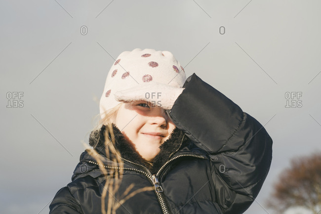 Portrait of cute girl shielding eyes from sunlight while wearing warm clothing