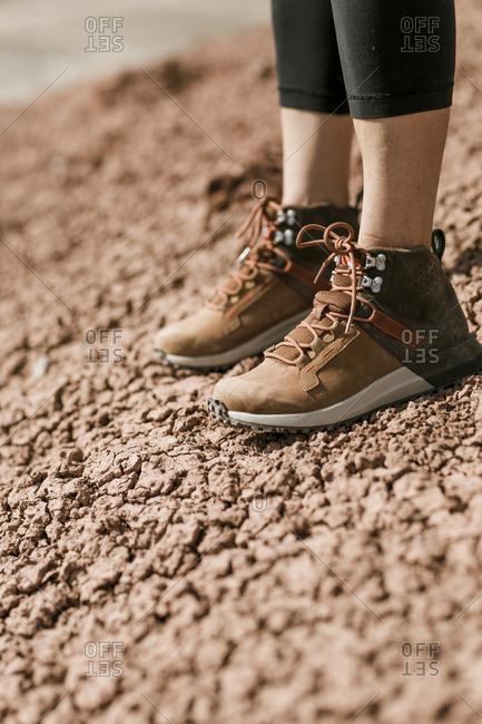 Low section of hiker standing on barren desert