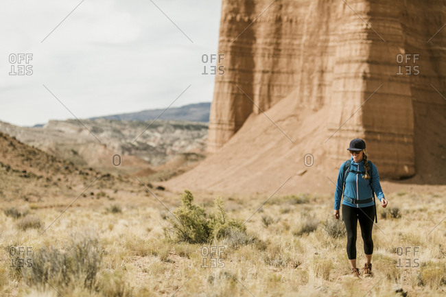 Full length of female hiker hiking at desert against rock formations