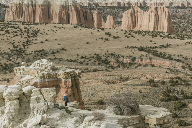 Mid distance view of carefree hiker hiking against rock formations at desert