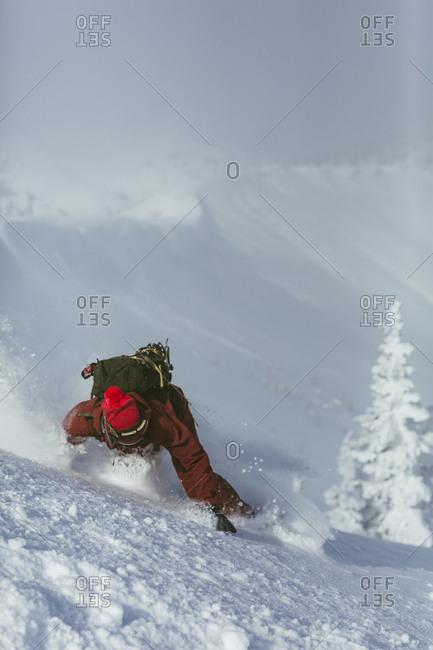 Hiker falling while skiing on ski slope during winter