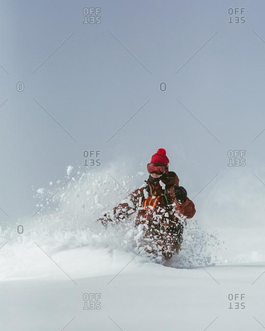 Hiker skiing on ski slope against sky during winter