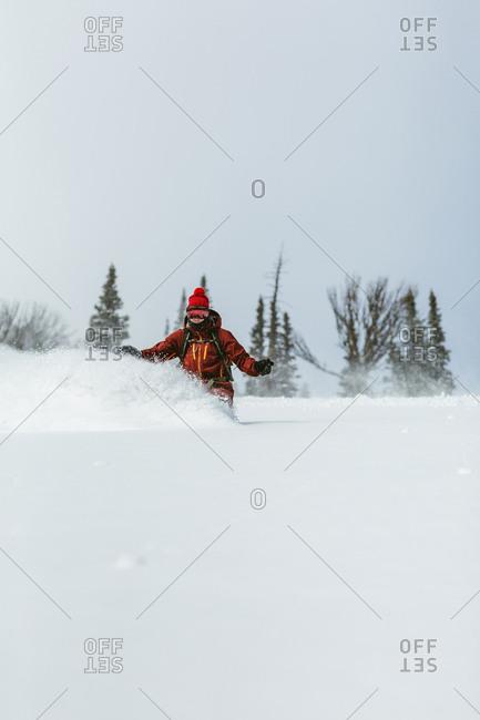 Hiker skiing on ski slope against sky