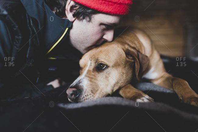 Close-up of man kissing dog at home