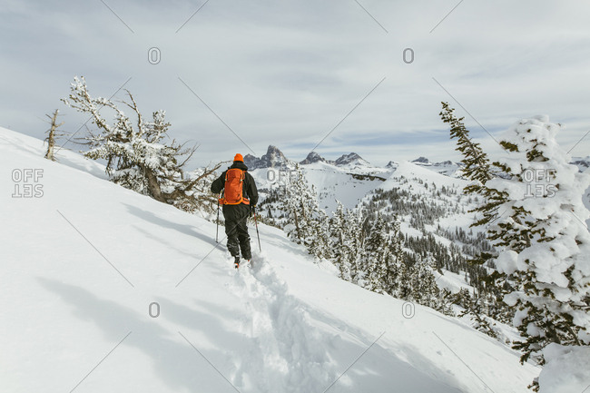 Rear view of hiker with backpack using ski poles while walking on snowcapped mountain