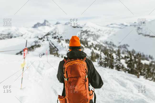 Rear view of hiker with backpack on snowcapped mountain during ski holiday