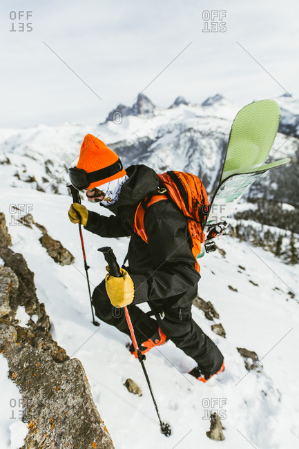 Hiker with backpack and ski poles climbing snowcapped mountain