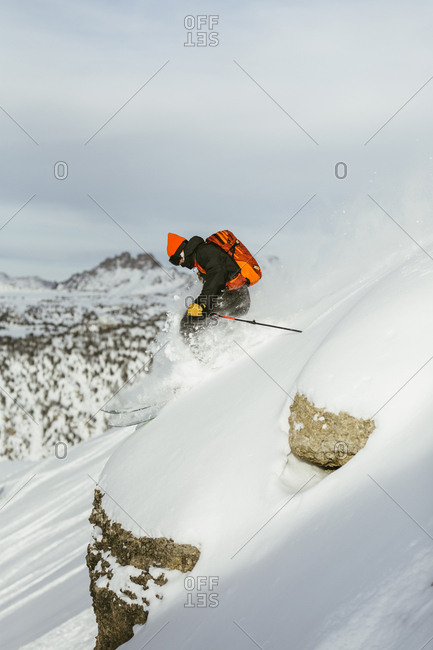 Side view of hiker with backpack skiing on snowcapped mountain