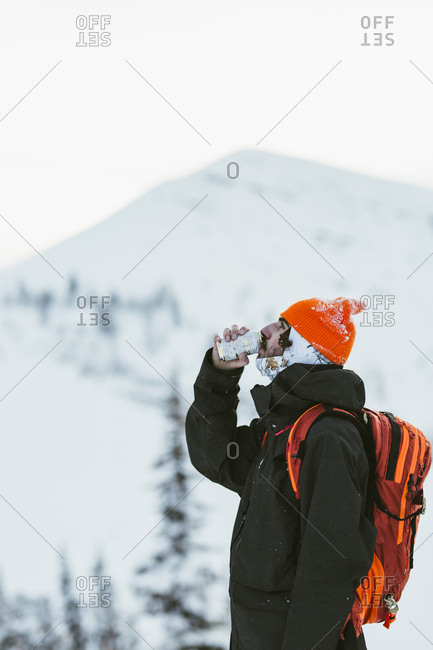Side view of hiker with backpack having drink from can while standing against snowcapped mountain