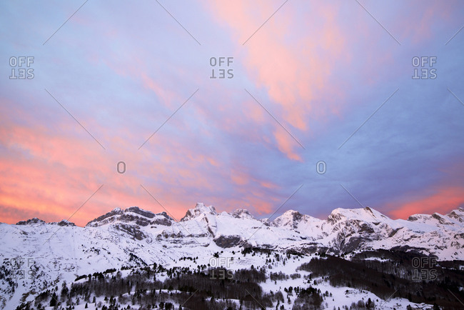 Low angle scenic view of snowcapped mountains against dramatic sky during sunset