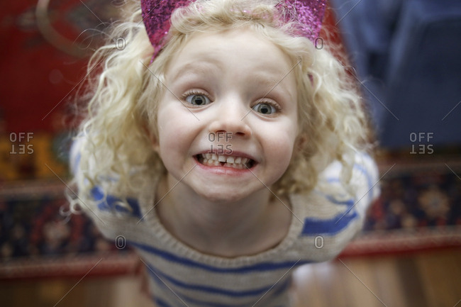 High angle portrait of cute girl showing gap toothed at home