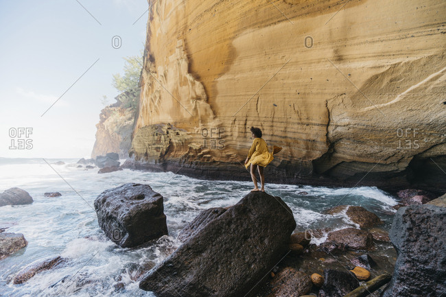 Side view of woman standing on rock at Reunion island