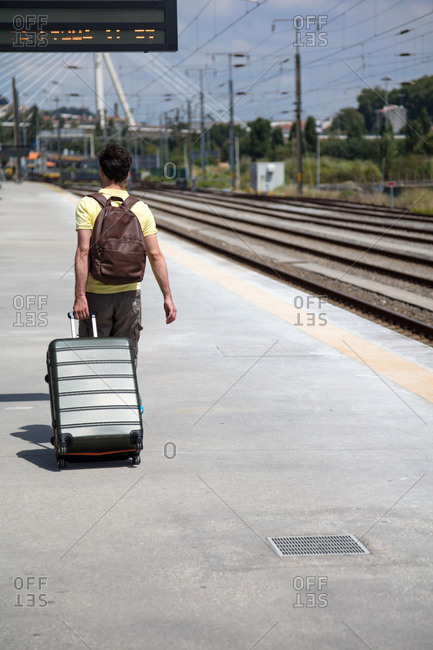 Young traveler pulling suitcase along train station platform